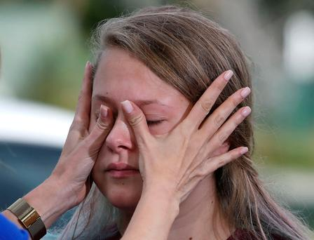 A student has her tears wiped away after recounting her story about the mass shooting at the Marjory Stoneman Douglas High School