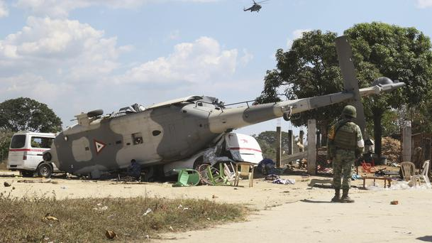 A soldier guards a downed helicopter in Santiago Jimitepec, Oaxaca state