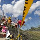 A woman places flowers near Marjory Stoneman Douglas High School (Gerald Herbert/AP)