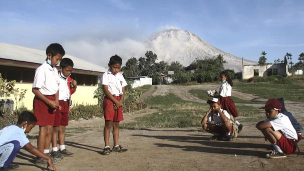 Students play before the start of class as Mount Sinabung is seen in the background (Ahmad Putra/AP)
