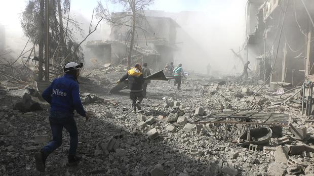 Members of the Syrian Civil Defence run to help survivors in Ghouta, Syria (Syrian Civil Defence White Helmets via AP)