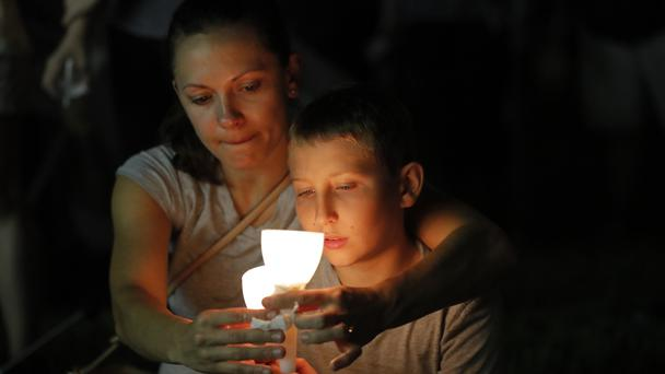 People participate in a candlelight vigil in memory of the 17 people killed at Marjory Stoneman Douglas High School in Parkland, Florida (AP)