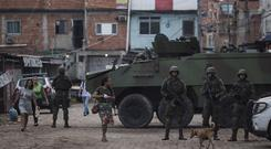 Brazilian marines stand in guard next to a vehicle during a surprise operation in Kelson's slum in Rio de Janeiro (AP)