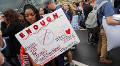 Tyra Hemans, 19, left, and Logan Locke, 17, right, students who survived the shooting at Stoneman Douglas High School, wait to board buses in Parkland (Gerald Herbert/AP)