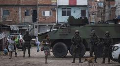 Brazilian marines stand in guard during surprise operation in Kelson's slum in Rio de Janeiro (AP Photo/Leo Correa)