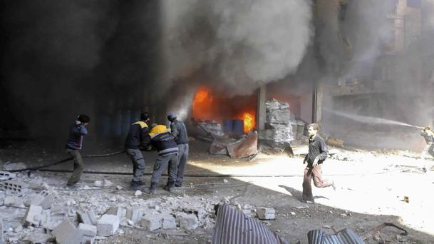 White Helmet members extinguishing a store fire during airstrikes (Syrian Civil Defence White Helmets via AP)