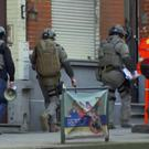Belgium security personnel enter a building in Brussels (AP)