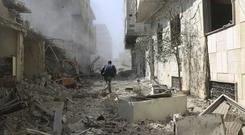 A Syrian man runs between destroyed buildings in Ghouta (Ghouta Media Center via AP)