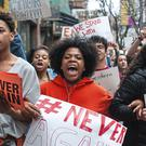 High school students Mia Arrington, centre, and Cheyenne Springette, right, lead chants as they march down Liberty Avenue in Pittsburgh during a walk-out in solidarity with other high schools across the country to show support for Parkland students (Stephanie Strasburg/Pittsburgh Post-Gazette via AP)