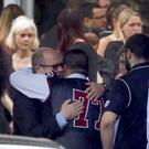 Mourners console each other during the funeral service for Marjory Stoneman Douglas High School assistant football coach Aaron Feis (Mike Stocker/AP)