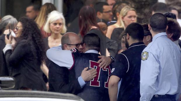 Mourners console each other during the funeral service for Marjory Stoneman Douglas High School assistant football coach, Aaron Feis (AP)