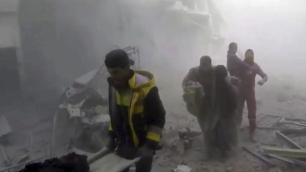 Members of the Syrian Civil Defence help residents during air strikes and shelling by Syrian government forces, in Ghouta (Syrian Civil Defence White Helmets via AP)