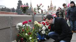 Activist Ilya Yashin lays flowers at the place where Russian opposition leader Boris Nemtsov was gunned down (Alexander Zemlianichenko/AP)