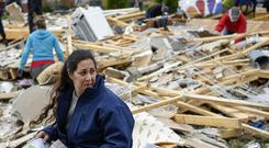 Kim Nicholson sifts through the debris of her home in Clarksville (AP)