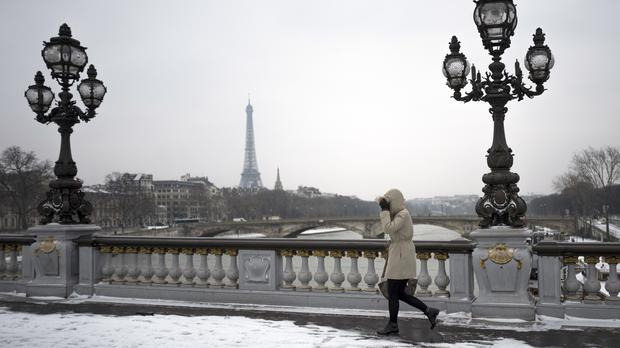 A pedestrian walks on the Alexandre III bridge after overnight snowfalls, in Paris (AP)