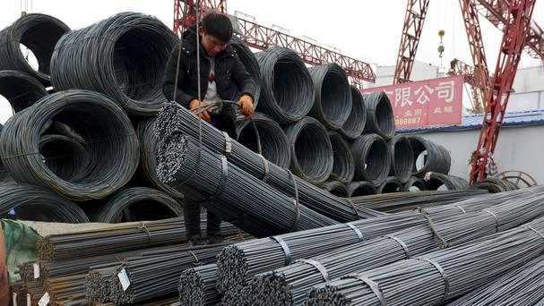 A worker loads steel products onto a vehicle at a steel market in Fuyang in central China's Anhui province (AP)
