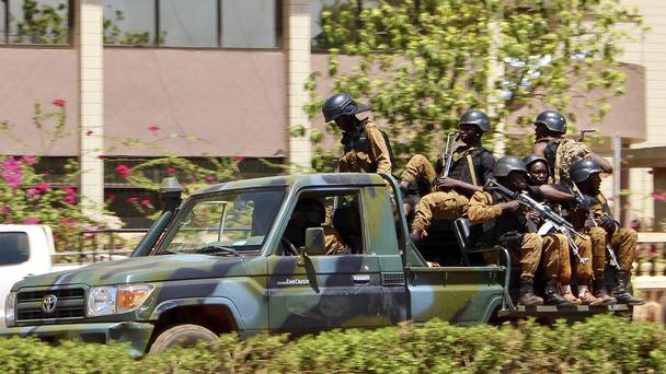 Troops ride in a vehicle near the French embassy in central Ouagadougou (AP)