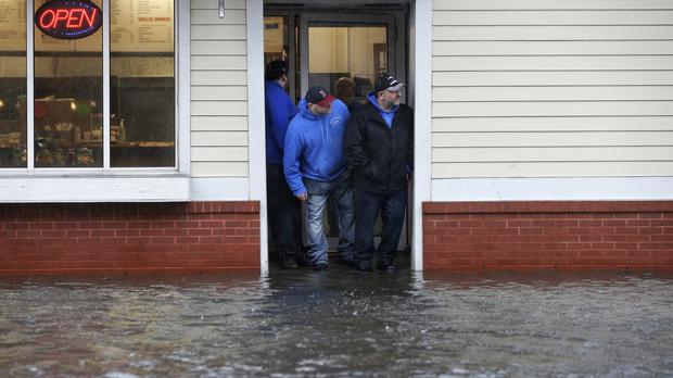 The entrance of a pizza shop as water floods a street in Scituate, Massachusetts (Steven Senne/AP)