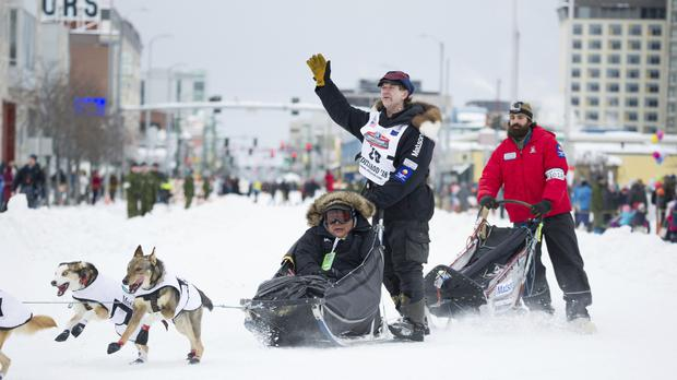 Iditarod musher Allen Moore waves to the crowd during the ceremonial start of the Iditarod Trail Sled Dog (Michael Dinneen/AP)