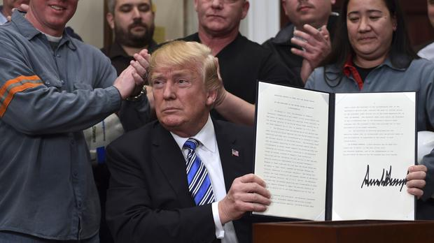 US President Donald Trump holds up a proclamation on steel imports at the White House (Susan Walsh/AP)