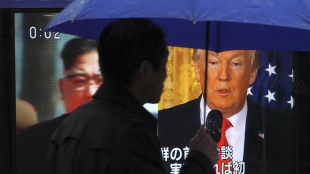 A man watches a TV screen showing North Korean leader Kim Jong Un, left, and US President Donald Trump in Tokyo (Eugene Hoshiko/AP)