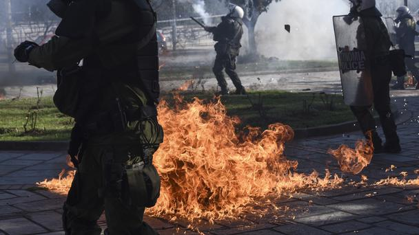 A molotov cocktail explodes between riot policemen during clashes with protesters outside the University of Thessaloniki (AP)