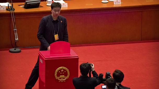 A staff member stands in front of a ballot box on the rostrum before a plenary session of China's National People's Congress at the Great Hall of the People in Beijing (Mark Schiefelbein/AP)