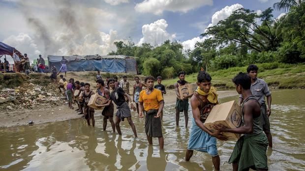 File photo of Rohingya Muslims carry food items (Dar Yasin/AP)