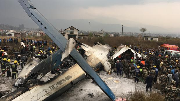 Nepalese rescuers stand near a passenger plane from Bangladesh that crashed at the airport in Kathmandu (AP Photo/Niranjan Shreshta)