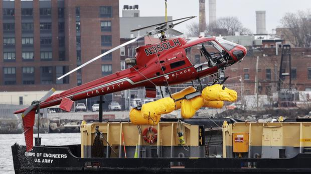 A helicopter is hoisted by crane from the East River onto a barge (Mark Lennihan/AP/PA)