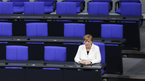 German Chancellor Angela Merkel sits in the government bench in the Bundestag in Berlin (AP Photo/Markus Schreiber)