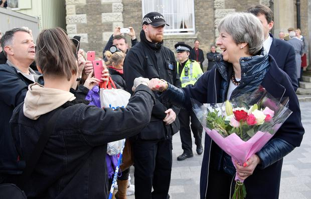 Britain's Prime Minister Theresa May greets people after visiting the scene where former Russian intelligence officer Sergei Skripal and his daughter Yulia were found after they were poisoned with a nerve agent, in Salisbury. Photo: Reuters