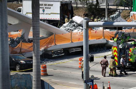 Vehicles are seen trapped under the collapsed pedestrian bridge. Photo: Joe Raedle/Getty