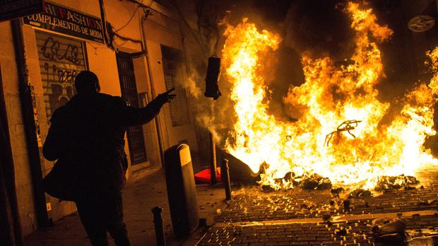 A protester throws rubbish at a burning barricade (AP/Alejandro Martinez Velez)
