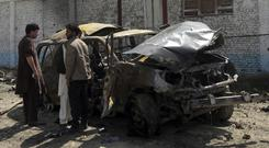 Officials inspect the site of a suicide car bomb in Kabul (Massoud Hossaini/AP)