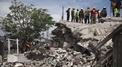 Rescue workers work to remove the debris on the collapsed building (Sayyid Abdul Azim/AP)