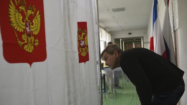 A polling station official checks vote cabins for the 2018 Russian presidential election (AP Photo)