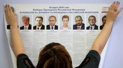 A polling station employee hangs a list of candidates for the 2018 Russian presidential election during preparations for the election at a polling station in St Petersburg, Russia. Photo: AP