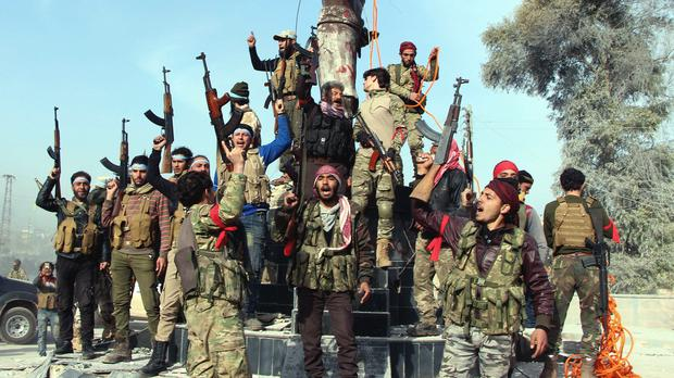 Turkey-backed Free Syrian Army soldiers celebrate around a statue of Kawa, a mythology figure in Kurdish culture as they prepare to destroy it in Afrin, Syria, (Hasan Kırmızitaş/DHA-Depo Photos via AP)