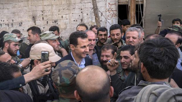 Syria's President Bashar Assad speaks with troops during a visit to the front line in the newly captured areas of eastern Ghouta, near the capital Damascus (AP)