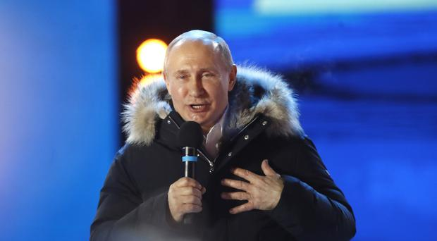 Russia's President Vladimir Putin gestures as he speaks to supporters during a rally near the Kremlin in Moscow (Pavel Golovkin/AP)