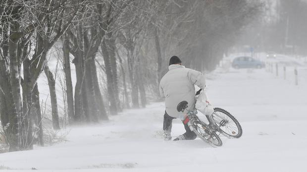 A man struggles to push his bicycle on a snow-covered road near Hajdunanas, east of Budapest (AP)