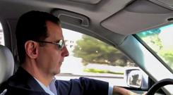 Syrian president Bashar Assad drives himself to the newly captured areas of eastern Ghouta (AP)