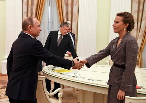Russian President Vladimir Putin shakes hands with one of his defeated opponents, Ksenia Sobchak. Photo: Reuters
