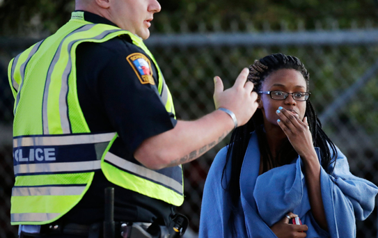 An employee talks to a police officer after she was evacuated at a FedEx distribution centre in Schertz, Texas. Photo: AP
