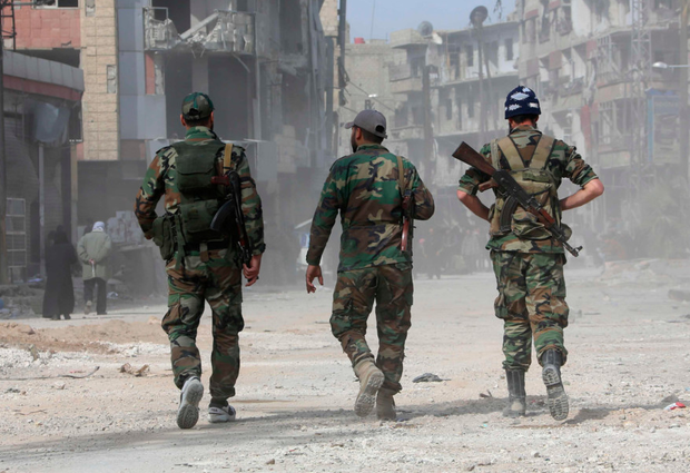 Government forces walk in the eastern Ghouta town of Kafr Batna. Photo: Getty
