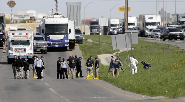 Officials investigate the scene where a suspect in a series of bombing attacks in Austin blew himself up (Eric Gay/AP)