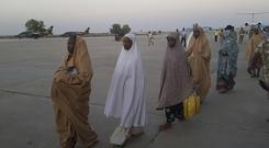 Freed girls board a military plane following a handover to government officials in Maiduguri, Nigeria (Hamza Suleiman/AP)