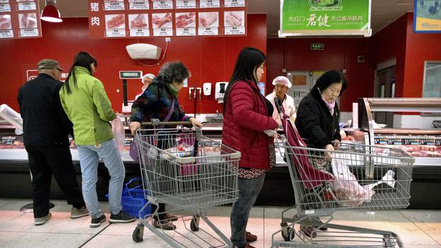 Customers shop for pork at a supermarket in Beijing (AP Photo/Mark Schiefelbein)