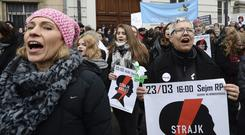 Protesting women shout slogans against efforts by the nation's conservative leaders to tighten Poland's already restrictive abortion law (Alik Keplicz/AP)